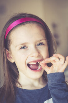 Portrait of smiling little girl with tooth gap holding milk tooth in her hand - SARF001348