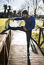 Spain, Gijon, athlete stretching in park - MGOF000127