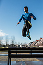 Spain, Gijon, athlete jumping over park bench - MGOF000125