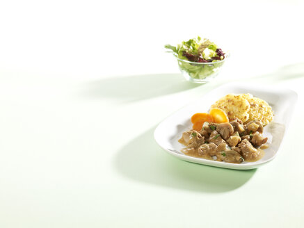 Dish of meat cut into strips and bowl of salad - SRSF000537