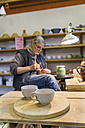 Potter in workshop with cups in foreground - TCF004553