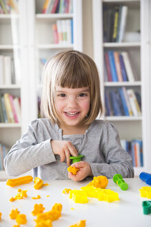 Portrait of smiling little girl playing with yellow modeling clay - LVF002869