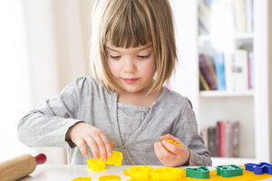 Little girl cutting out yellow modeling clay - LVF002850