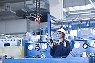 Technician in factory hall using regulator for hook - SGF001327