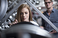 Female customer inspecting a tyre in a tyre shop - ZEF003995