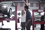 Man showing female customer the tyre fitment process - ZEF003998