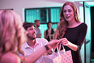 Portrait of young woman receiving a gift at party - ZEF003404