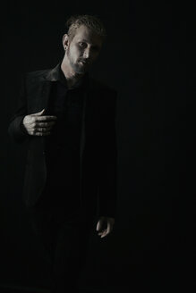 Man wearing black clothes in front of black background - VE000030