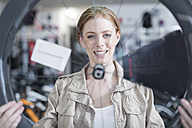 Young woman in bicycle shop looking for bike - ZEF005035