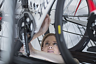 Young woman in bicycle shop looking for bike - ZEF005041