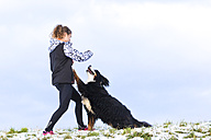 Young woman playing with her Saint Bernard on snow-covered meadow - STSF000698