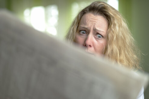 Horrified woman reading newspaper - FRF000200