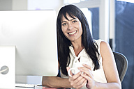 Portrait of smiling woman at desk in an office - ZEF003553
