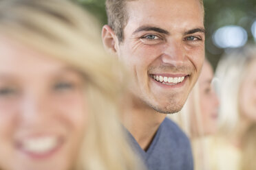 Smiling young man among frinds outdoors - ZEF004616