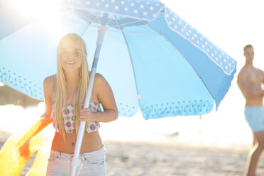 Happy young woman holding beach umbrella - ZEF004621