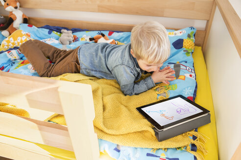 Little boy lying on his bed looking at digital tablet with child's drawing - MFF001490