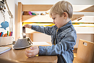Little boy using MP3 Player and docking station for listening music in his nusery - MFF001493