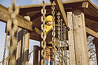 Little boy walking along a hanging bridge on a playground - MFF001502