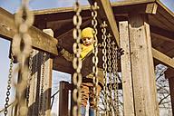 Little boy walking along a hanging bridge on a playground - MFF001502