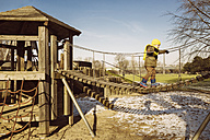Little boy walking along a hanging bridge on a playground - MFF001503