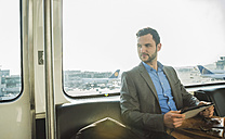 Germany, Frankfurt, young businessman in bus at the airport - UU003422