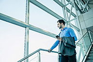 Young businessman with cell phone looking out of window - UUF003455