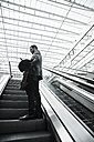 Young businessman with digital tablet on escalator - UU003429