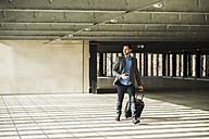 Young businessman with baggage walking in car park - UU003444