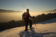 Austria, Tyrol, Schwaz, woman snowshoeing at sunset - MKFF000170