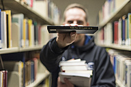 Man showing book in library - CHP000104