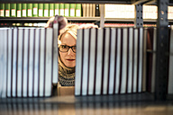 Woman in library looking from behind bookshelf - CHPF000105