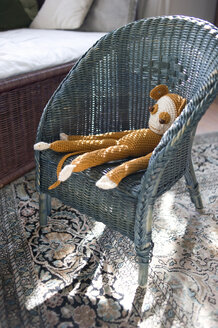 Crocheted toy monkey on wicker chair - GIS000031