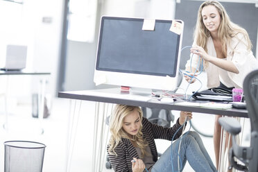 Creative office women trying to connect a network cable under her desk - ZEF003010