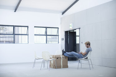Creative office man relaxing on a chair and boxes - ZEF003012