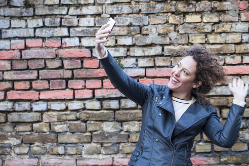 Smiling woman taking selfie in front of brick wall - ANHF000003