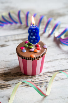 Birthday muffin with chocolate buttons and lighted candle - SARF001405
