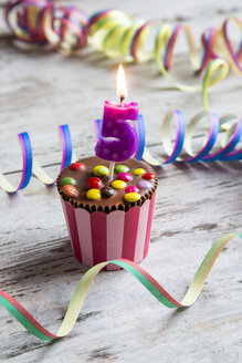 Birthday muffin with chocolate buttons and lighted candle - SARF001414