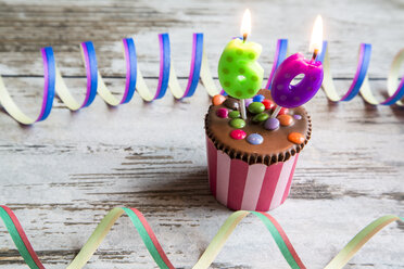 Birthday muffin with chocolate buttons and lighted candles - SARF001420