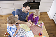 Father tinkering in kitchen with son and daughter - RHF000562