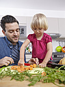 Father preparing food in kitchen with daughter - RHF000580