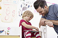 Little girl sitting on bunk bed, drawing on touch pad, father watching - RHF000588