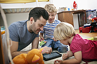 Father and children using mini tablet, lying on floor - RHF000605