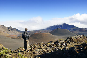 USA, Hawaii, Maui, Haleakala, man looking at volcanic landscape with cinder cones - BRF001075