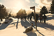 Spain, Catalonia, Cadi-Moixero Natural Park, group of people hiking in snow at sunset - GEM000060