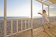 Portugal, Algarve, woman doing yoga exercises at beach house at sunset - MSF004497