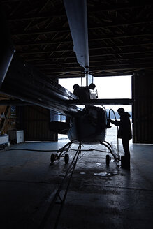 Man preparing helicopter in hangar - KDF000701