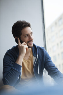 Portrait of smiling man telephoning with smartphone while looking through window - RBF002483