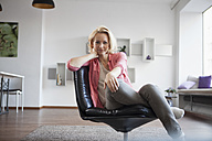 Portrait of woman sitting on leather chair at home - RBF002488