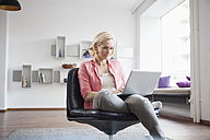 Woman sitting with laptop on leather chair at home - RBF002491
