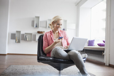 Woman with laptop and credit card sitting on leather chair at home - RBF002494
